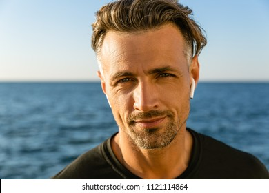 close-up portrait of smiling adult man with wireless earphones on seashore looking at camera