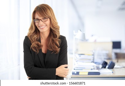 Close-up portrait of a smiling attractive mature business woman with arms crossed standing in her office