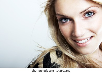 Close-up portrait of a smiling beautiful blonde caucasian woman with blue eyes, looking at camera, on a gray background with copy-space