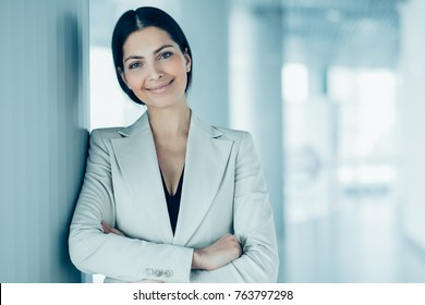 Closeup portrait of smiling beautiful middle-aged business woman wearing jacket, looking at camera, leaning on column and standing in light office hall with her arms crossed. Front view.