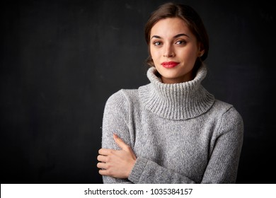 Close-up portrait of smiling beautiful woman posing at dark background with copy space.