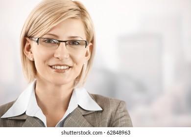 Closeup portrait of smiling blonde businesswoman wearing glasses.?