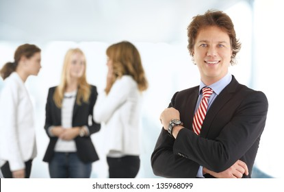 Close-up portrait of smiling businessman with colleagues in the background