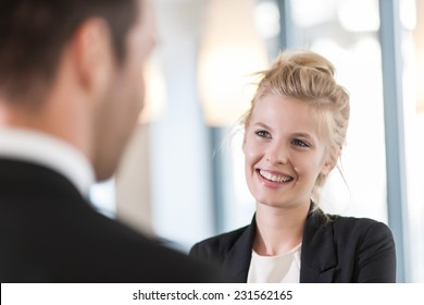 close-up portrait of a smiling businesswoman talking with a man