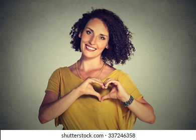 Closeup portrait smiling cheerful happy young woman making heart sign with hands isolated grey wall background. Positive human emotion expression feeling life perception attitude body language