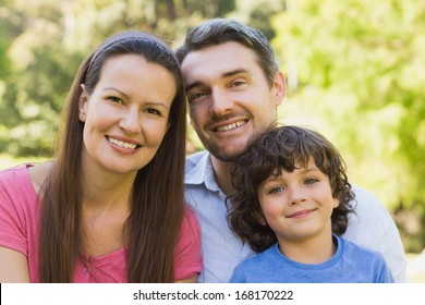 Close-up portrait of a smiling couple with son in the park