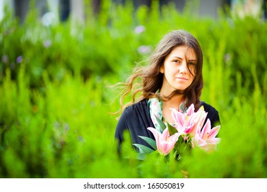 Closeup portrait of a smiling dark-haired young girl holding a bouquet of pink lilies in her hands on green blurry bokeh background