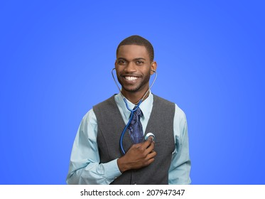 Closeup portrait smiling executive man, business person, worker listening to his heart with stethoscope isolated blue background. Preventive medicine, financial condition concept. Face expressions