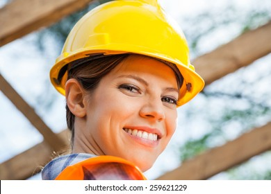 Closeup portrait of smiling female construction worker at site