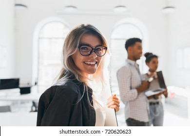 Close-up portrait of smiling female student in trendy glasses holding documents on blur background. Black young man working as manager carrying laptop to office.