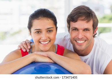 Closeup portrait of a smiling fit couple with exercise ball at a bright gym