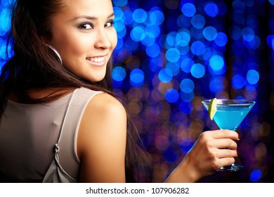 Close-up portrait of a smiling girl holding a cocktail