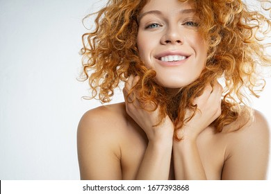 Closeup portrait of a smiling girl with naked shoulders touching her hair with both hands