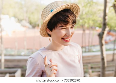 a92d3623c0b Close-up portrait of smiling girl wearing trendy straw hat and rings  walking outside after