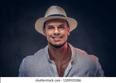 Close-up portrait of a smiling handsome fashionable bearded man in a white shirt and panama hat.