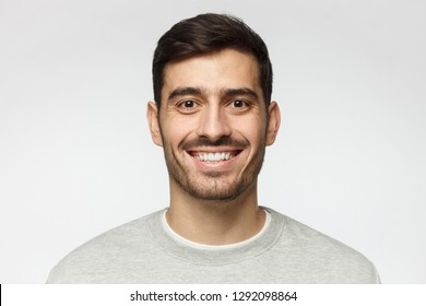 Close-up portrait of smiling handsome man  isolated on gray background