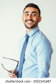 Closeup portrait of smiling handsome young man holding glasses. Successful businessman concept. Isolated side view on grey background.