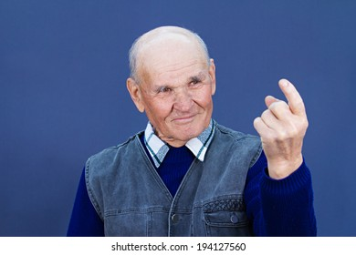 Closeup portrait, smiling, happy, elderly, senior, old man, grandfather giving come here sign with hand, finger, asking someone to approach him, help, isolated blue background. Human expression