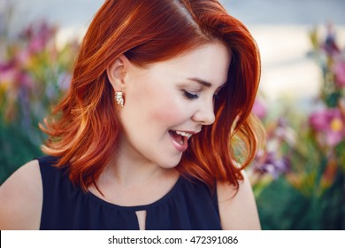 Closeup portrait of smiling laughing flirty middle aged white caucasian woman with waved curly red hair in black dress screaming outside in park, beauty fashion lifestyle concept
