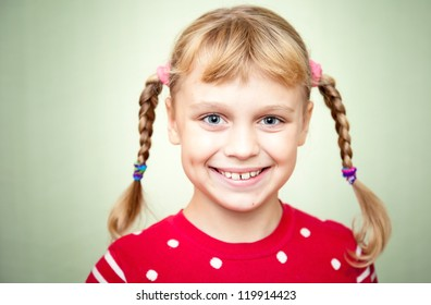 Closeup portrait of smiling little blond girl with pigtails