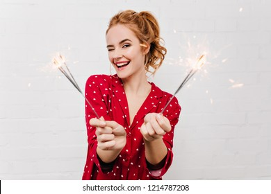 Close-up portrait of smiling lovable girl celebrating new year with sparklers. Studio shot of graceful woman in funny red pajamas waiting for christmas.