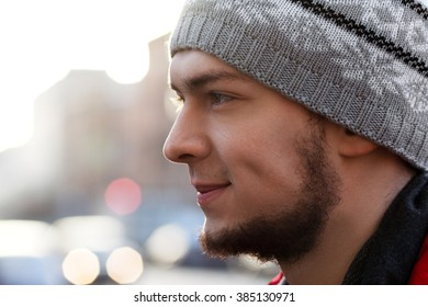 Closeup portrait of smiling man with beard in black coat and scarf in street