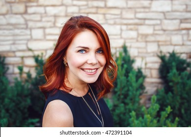 Closeup portrait of smiling middle aged white caucasian woman with waved curly red hair in black dress looking in camera outside in park garden, beauty fashion lifestyle concept