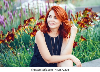 Closeup portrait of smiling middle aged white caucasian woman with waved curly red hair in black dress looking away outside in park garden among flowers, beauty fashion lifestyle concept