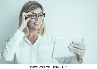 Closeup portrait of smiling middle-aged attractive fair-haired woman adjusting glasses, holding tablet computer and reading news on it. Important news concept. Isolated front view on grey background.