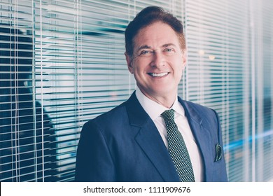Closeup portrait of smiling middle-aged business man looking at camera and standing with glass partition in background
