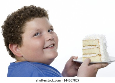 Closeup portrait of a smiling overweight boy holding large slice of cake