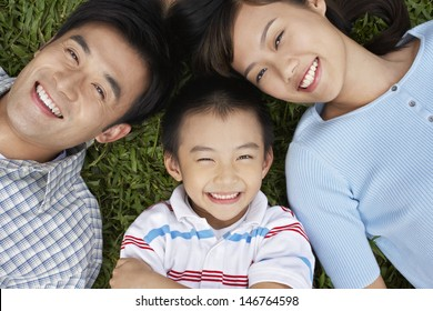 Closeup portrait of smiling parents with son lying on grass