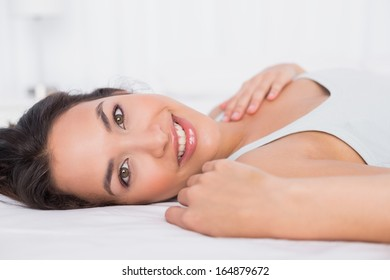 Close-up portrait of a smiling pretty young woman relaxing in bed