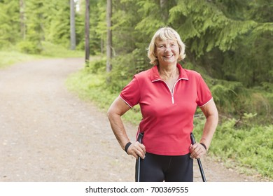 Close-up portrait of a smiling senior woman nordic walking through the forest and enjoying healthy lifestyle.