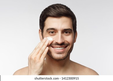 Close-up portrait of smiling shirtless young man applying facial cream, isolated on gray background. Skin care concept