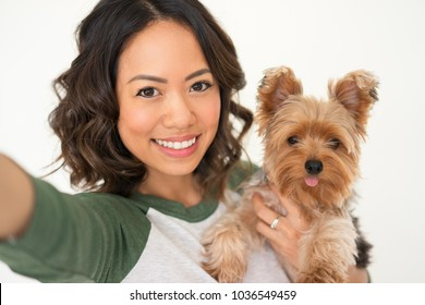 Closeup portrait of smiling young attractive woman holding Yorkshire terrier and taking selfie photo. Yorkshire terrier concept. Isolated front view on white background.