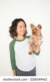 Closeup portrait of smiling young attractive woman holding Yorkshire terrier. Yorkshire terrier concept. Isolated front view on white background.
