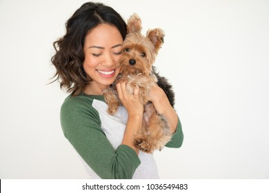 Closeup portrait of smiling young attractive woman embracing Yorkshire terrier with her eyes closed. Yorkshire terrier concept. Isolated front view on white background.