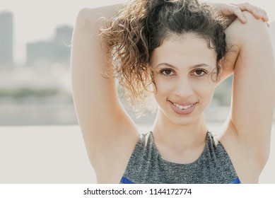 Closeup portrait of smiling young attractive woman looking at camera, wearing sportswear, exercising, stretching arm and standing outdoors. Front view.