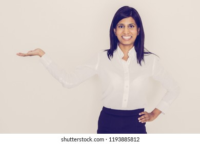 Closeup portrait of smiling young beautiful black-haired woman looking at camera and holding empty space on palm. Product concept. Isolated front view on white background.