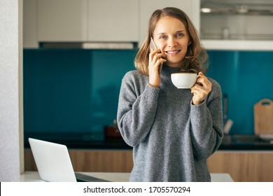 Closeup portrait of smiling young beautiful woman looking at camera, standing, drinking coffee and talking on smartphone in kitchen. Leisure at home concept. Front view.
