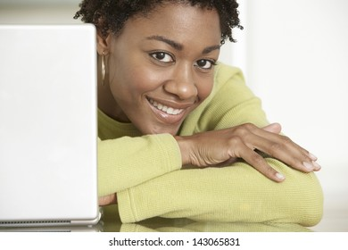 Closeup portrait of smiling young businesswoman with laptop on table