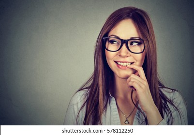 Closeup portrait of a smiling young flirting woman with finger on lips looking sideways isolated on gray background with copy space. Human emotions