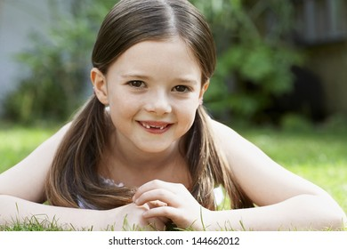 Closeup portrait of smiling young girl lying in grass