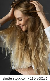 Closeup portrait of a smiling young pregnant beautiful blonde woman wearing a white shirt joyfully touching her hands with her hair. Clean, healthy skin. Fashionable, commercial design. Copy space.