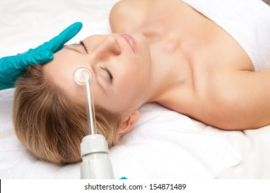 closeup portrait of smiling young woman and medical device touching her face
