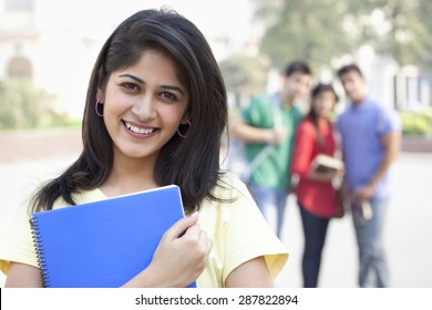 Close-up portrait of smiling young woman with friends in the background