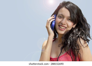 Close-up portrait of smiling young woman with mobile phone