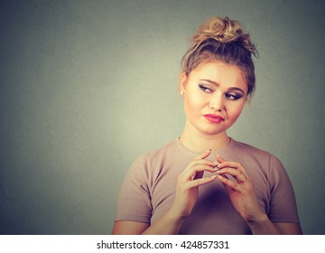 Closeup portrait of sneaky, sly, scheming young woman plotting something isolated on gray background. Negative human emotions, facial expressions, feelings, attitude