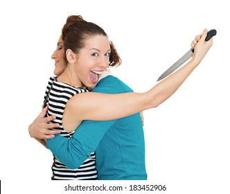 Closeup portrait, sneaky, sly young woman hugging lady, at same time trying to stab her in back, isolated white background. Negative human emotion facial expression, feelings